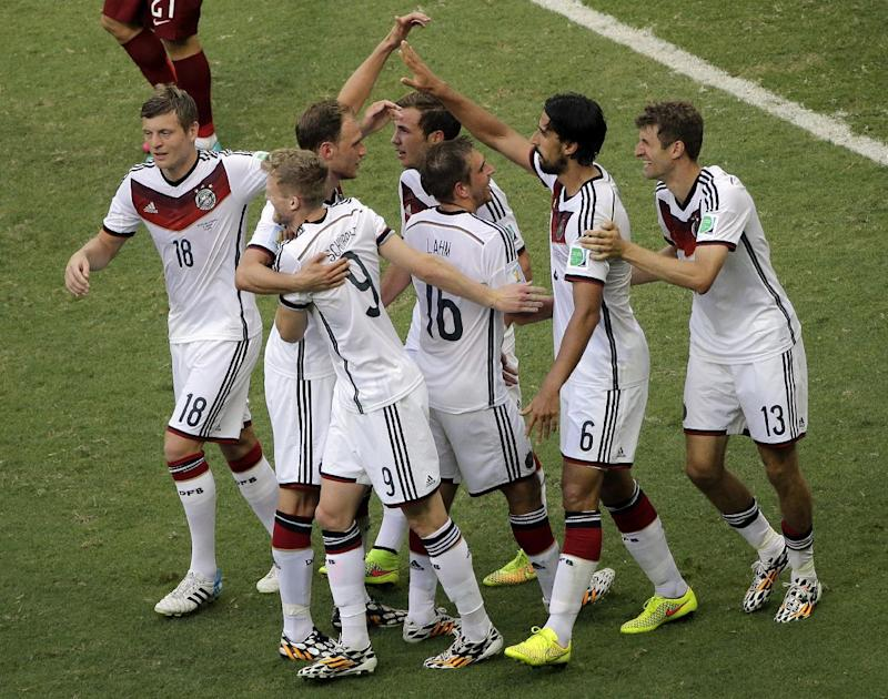 Teammates celebrate with Germany's Thomas Mueller, right, after his scored his third goal and the team's fourth during the group G World Cup soccer match between Germany and Portugal at the Arena Fonte Nova in Salvador, Brazil, Monday, June 16, 2014