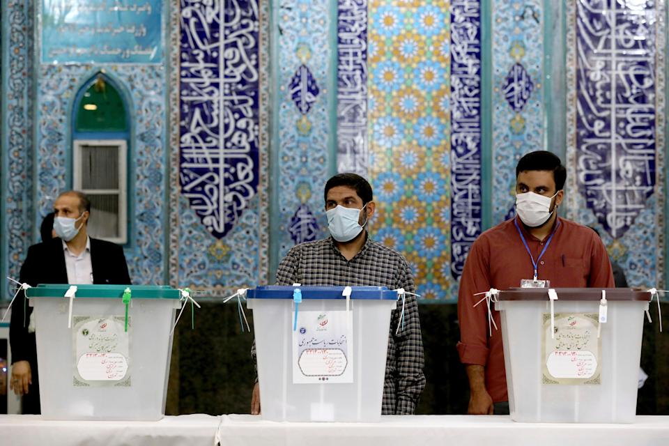 Iranian election officials wait for voters during the presidential election at a polling station in Tehran (AP)
