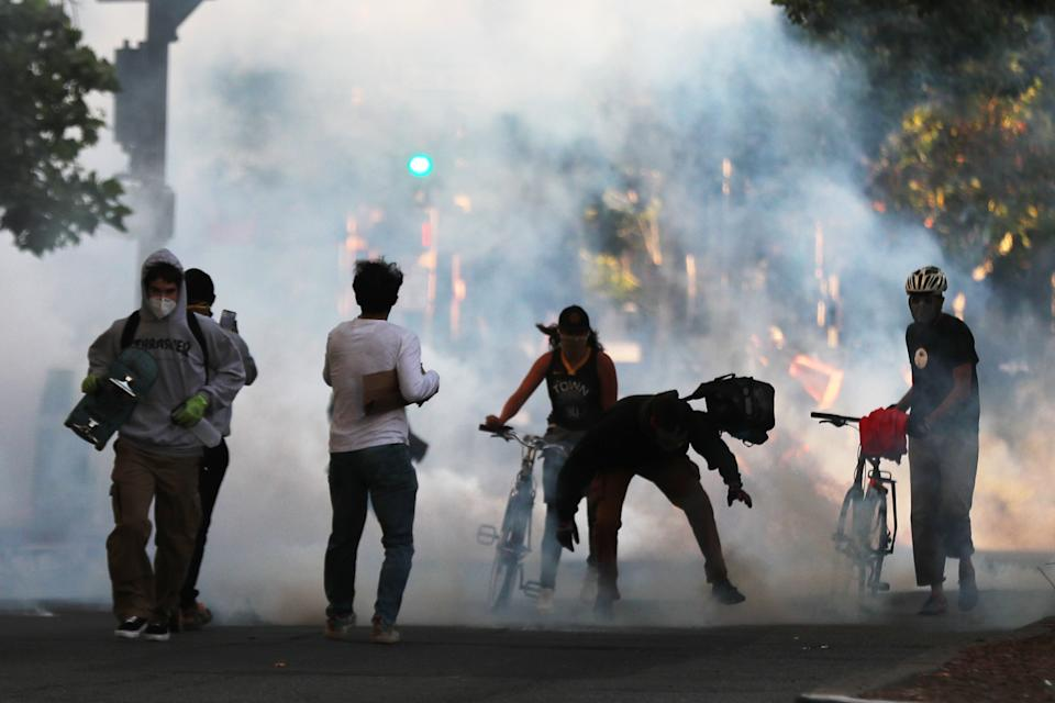Some protesters move away as police shoot tear gas and flash grenades to disperse the crowd on Broadway near the Oakland Police Department during the fourth day of protests over George Floyd's death by the Minneapolis police in Oakland, CA (Ray Chavez/Digital First Media/East Bay Times via Getty Images)