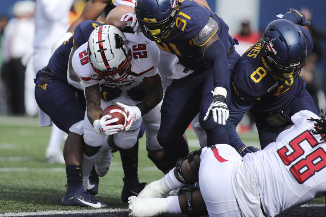 Texas Tech's Ta'Zhawn Henry (26) carries the ball past West Virginia's Reuben Jones (91) for a touchdown during the first quarter of their NCAA college football game in Morgantown, W.Va., Saturday, Nov. 9, 2019. (AP Photo/Chris Jackson)