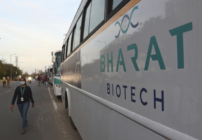"""An employee of Bharat Biotech walks to board a bus parked outside the office on the outskirts of Hyderabad, India, Saturday, Jan. 9, 2021. There has been growing apprehensions among health care workers after India took a regulatory shortcut to approve a vaccine by the Indian drugmaker before late clinical trials showed it was effective in preventing illness from coronavirus infections. The panel of experts that eventually gave the nod to the vaccine had met three times. In the first two meetings, on Dec. 30 and Jan. 1, they were dissatisfied with Bharat Biotech's application and asked for more data on its ability to prevent illness from COVID-19, minutes from the meeting show. But the next day, the experts permitted the restricted use of the Bharat Biotech vaccine as an """"abundant precaution"""" after the company claimed that the vaccine had the potential to target a more contagious variant of the virus found in Britain. (AP Photo/Mahesh Kumar A.)"""