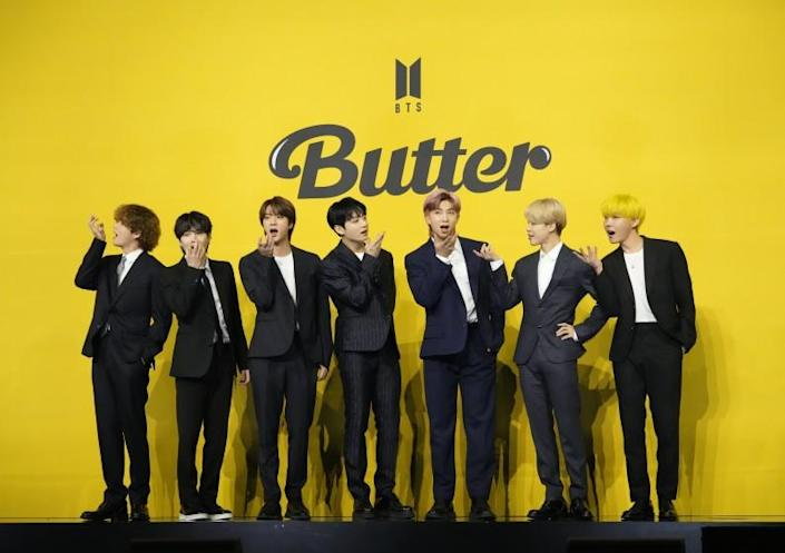 Seven men in dark suits posing against a yellow background