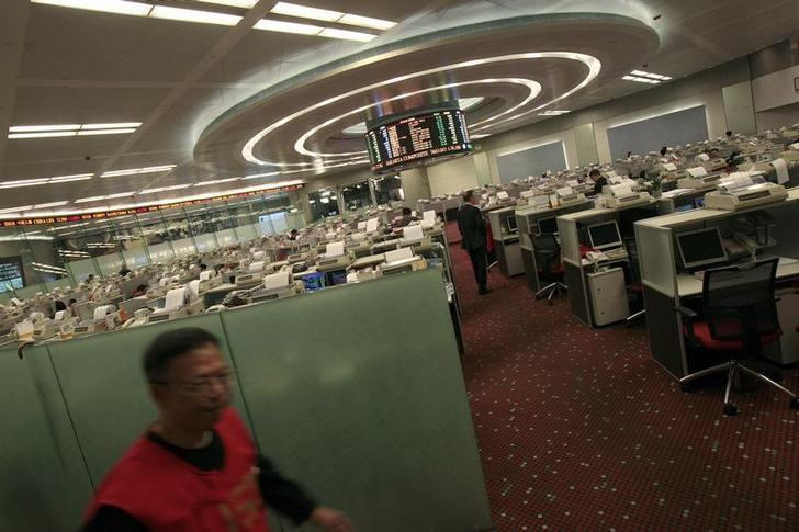 A floor trader (L) walks in the trading hall of the Hong Kong Stock Exchange November 23, 2010. REUTERS/Tyrone Siu/Files