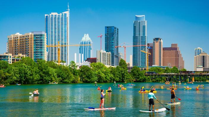 Austin, United States - May 3, 2014: People having fun on rowboats and boards in Lady Bird Lake on a nice day with the Austin skyline in the background.