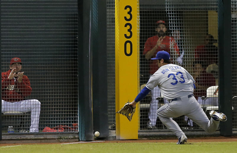 Los Angeles Dodgers left fielder Scott Van Slyke (33) chases down an RBI-single hit by Arizona Diamondbacks' Miguel Montero during the third inning of a baseball game on Thursday, Sept. 19, 2013, in Phoenix. (AP Photo/Matt York)