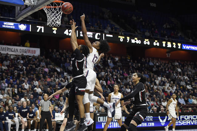 Connecticut's Christyn Williams (13) shoots over Cincinnati's Antoinette Miller, left, during the second half of an NCAA college basketball game in the American Athletic Conference tournament finals at Mohegan Sun Arena, Monday, March 9, 2020, in Uncasville, Conn. (AP Photo/Jessica Hill)