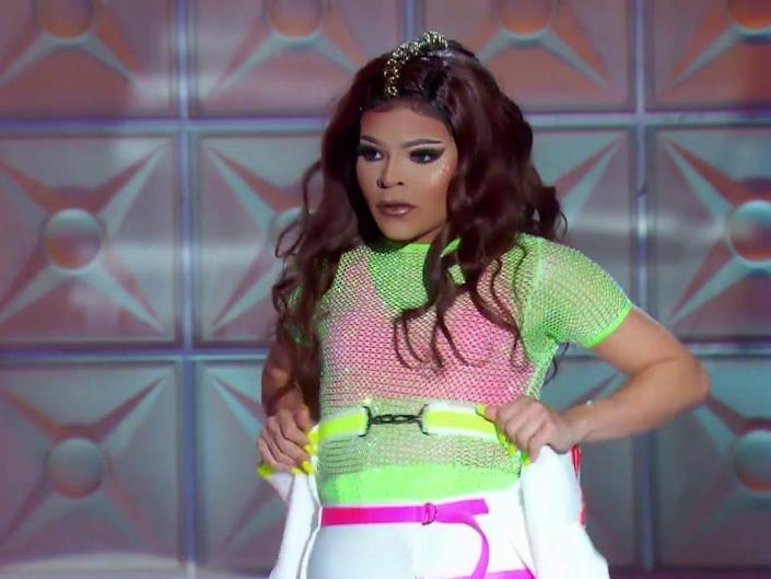 Vanessa Vanjie Matteo in green shirt and brown wig on stage at rupaul drag race