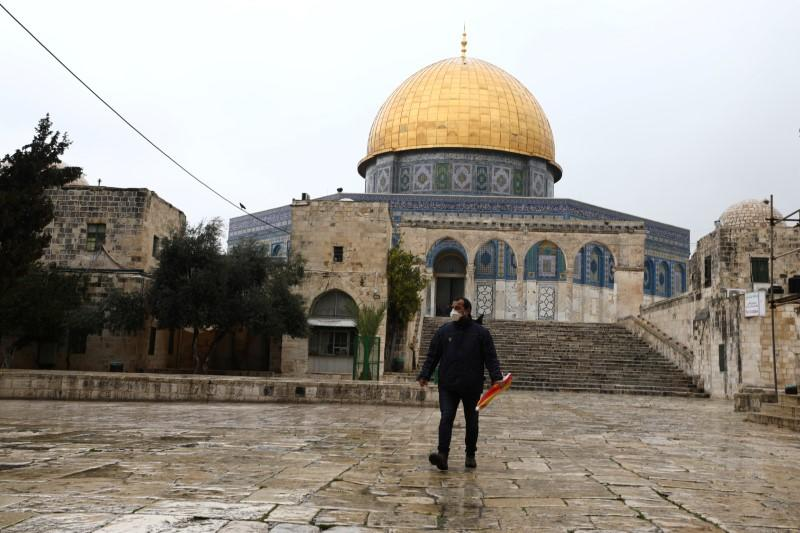 A man walks in front of the Dome of the Rock in the compound known to Muslims as Noble Sanctuary and to Jews as Temple Mount, in Jerusalem's Old City