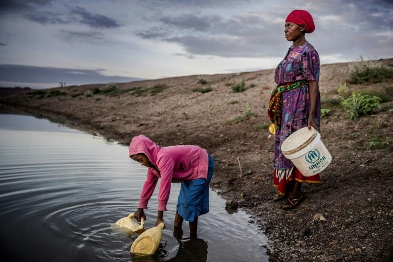 Martha Kasafi and her daughter, refugees from Democratic Republic of Congo, collect water for their crops in Kalobeyei settlement for refugees in  Kenya on October 2, 2019; Independent experts on the Human Rights Committee issued a non-binding ruling in a case brought by Ioane Teitiota from the Pacific island nation of Kiribati