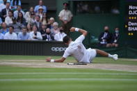 Serbia's Novak Djokovic falls while playing against Canada's Denis Shapovalov during the men's singles semifinals match on day eleven of the Wimbledon Tennis Championships in London, Friday, July 9, 2021. (AP Photo/Alberto Pezzali)