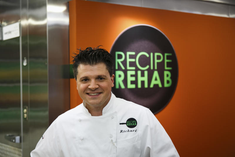 """In this Aug. 18, 2013 photo provided by Trium Entertainment, Lewisburg, W. Va., resident Rich Rosendale poses in front of a Recipe Rehab sign at the studios in Calabasas, Calif. Rosendale, one of TV's newest celebrity chefs, says his greatest challenges come on the set of """"Recipe Rehab,"""" a Saturday morning show that begins airing Sept. 28 on CBS. (AP Photo/Trium Entertainment, Venessa Stump)"""