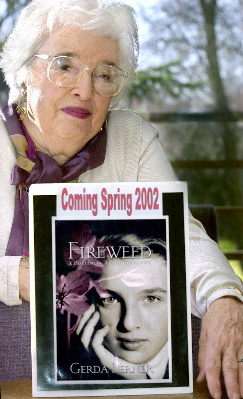 This 2001 photo shows  Gerda Lerner, founder of University of Wisconsin-Madison's graduate program in women's history, with an image of her autobiography, Fireweed. Lerner, a founding member of the National Organization for Woman and a pioneer in the field of women's history, has died at an assisted-living facility in Madison. She was 92. (AP Photo/Wisconsin State Journal, Sarah B. Tews)