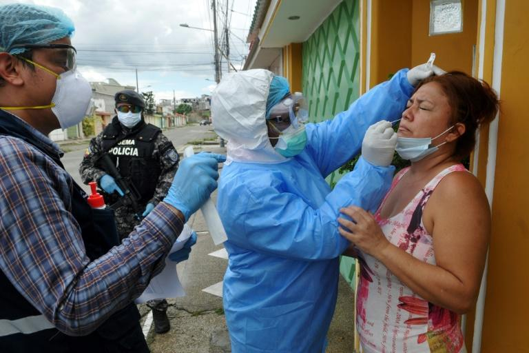 Health ministry personnel test a woman for the novel coronavirus in northern Guayaquil, Ecuador, on April 19, 2020 (AFP Photo/Jose SANCHEZ)