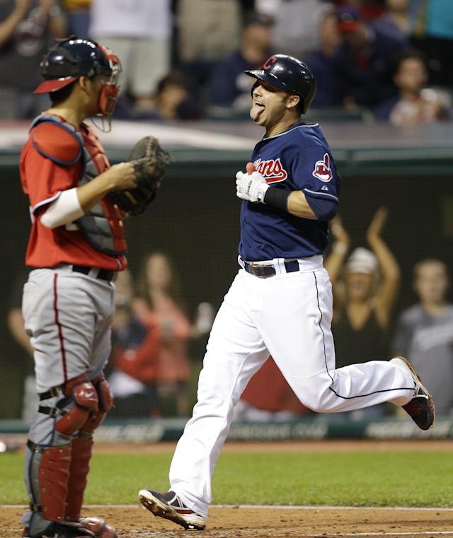 Cleveland Indians' Nick Swisher, right, scores on a two-run double by Michael Brantley in the fifth inning of a baseball game against the Washington Nationals, Saturday, June 15, 2013, in Cleveland. Nationals catcher Kurt Suzuki watches. (AP Photo/Tony Dejak)