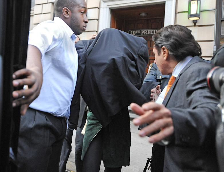 Lindsay Lohan, center, is escorted from the 10th Precinct police station, with her face shielded, Thursday, Nov. 29, 2012, in New York after being charged for allegedly striking a woman at a nightclub. Police say Lohan was arrested at 4 a.m. and charged with third-degree assault. They say she got into the argument with another woman at Club Avenue in Manhattan and struck the woman in face with her hand. (AP Photo/ Louis Lanzano)