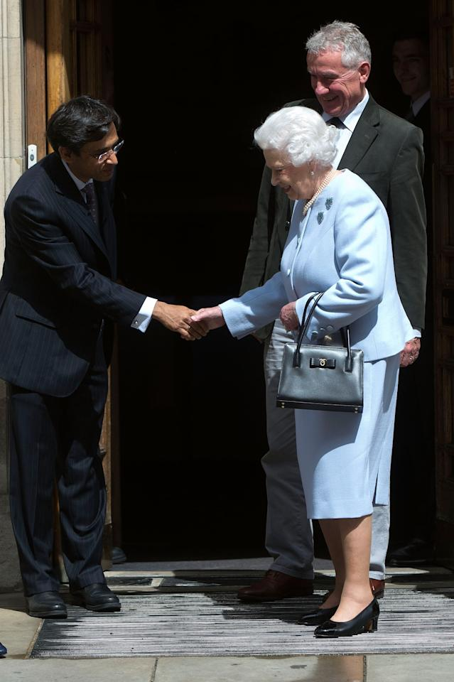 LONDON, ENGLAND - JUNE 15: Queen Elizabeth II shakes hands with a member of staff as she leaves the London Clinic after visiting her husband Prince Philip, Duke of Edinburgh on June 15, 2013 in London, England. The Duke of Edinburgh is recovering in hospital after undergoing exploratory abdominal surgery. (Photo by Bethany Clarke/Getty Images)