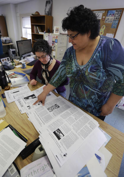 In this Wednesday, March 6, 2013 photo, editor Toni Ortiz, right, looks over pages with copy editor Teresa Malcolm while working in the newsroom of the National Catholic Reporter in Kansas City, Mo. The National Catholic Reporter, a newspaper known for unflinching coverage of the Catholic church scandal, was rebuked by a bishop in its own backyard after calling for his ouster in a battle that illustrates tensions between U.S. bishops and groups that call themselves Catholic but aren't sanctioned by the church. (AP Photo/Orlin Wagner)