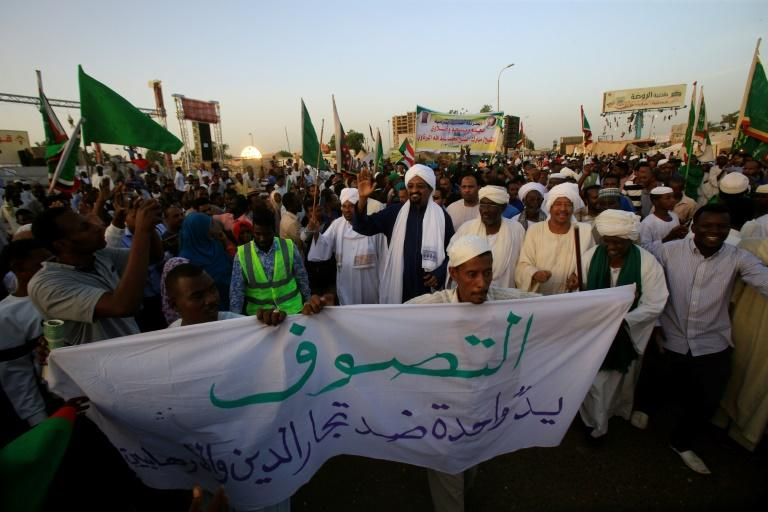 Members of the Sudanese Sufi community arrive for a sit-in outside the military headquarters in Khartoum