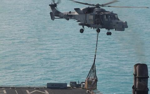 a Royal Navy Wildcat from 815 NAS (Naval Air Squadron) lifting off from the flight deck of RFA Mounts Bay with vital stores for Sandy Bay Village beach, Anguilla - Credit: Royal Navy