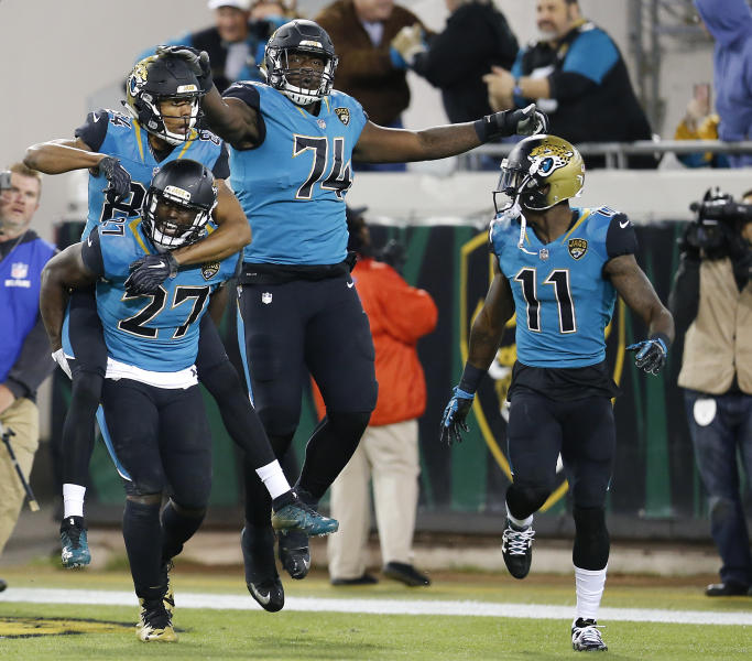 Jacksonville Jaguars wide receiver Keelan Cole, left, rides on the back of Leonard Fournette (27) as they celebrate with offensive lineman Cam Robinson (74) and wide receiver Marqise Lee (11) after scoring a touchdown against the Seattle Seahawks during the second half of an NFL football game, Sunday, Dec. 10, 2017, in Jacksonville, Fla. (AP Photo/Stephen B. Morton)