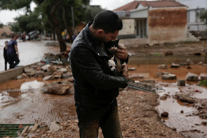 A local, carrying a dog in his jacket, holds a cat he saved from a tree, following a heavy rainfall in the town of Mandra. (Alkis Konstantinidis/Reuters)