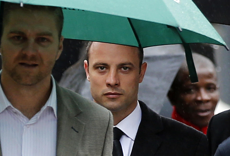 Olympic and Paralympic track star Oscar Pistorius (C) arrives at court ahead of the fifth day of his trial for the murder of his girlfriend Reeva Steenkamp at the North Gauteng High Court in Pretoria, March 7, 2014. REUTERS/Siphiwe Sibeko (SOUTH AFRICA - Tags: CRIME LAW SPORT ATHLETICS)