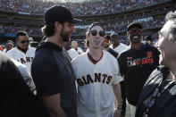 San Francisco Giants pitcher Madison Bumgarner, left, talks with former player Tim Lincecum during a ceremony honoring Giants manager Bruce Bochy after a baseball game between the Giants and the Los Angeles Dodgers in San Francisco, Sunday, Sept. 29, 2019. (AP Photo/Jeff Chiu, Pool)