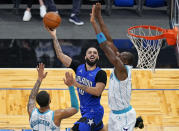 Orlando Magic guard Evan Fournier, center, makes a shot over Charlotte Hornets forward P.J. Washington, left, and center Bismack Biyombo, right, during the second half of an NBA basketball game, Sunday, Jan. 24, 2021, in Orlando, Fla. (AP Photo/John Raoux)