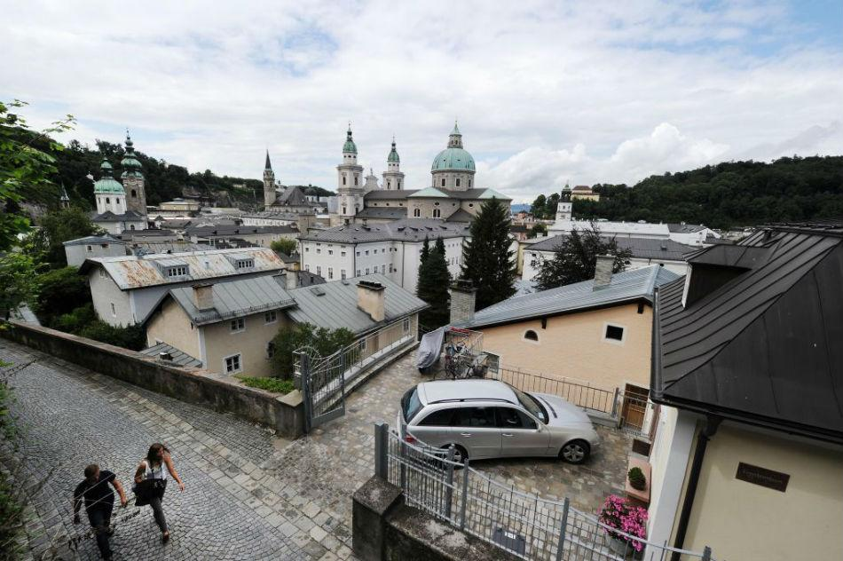 In front of the backdrop of the steeples of St. Peters convent (L), Franciscan church and Salzburg cathedral tourists walk up the old way to Salzburg castle Hohensalzburg.