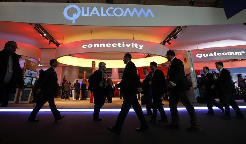 Visitors walk past the Qualcomm stand at the Mobile World Congress in Barcelona