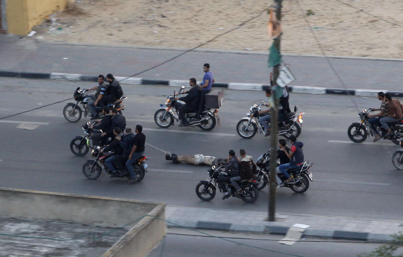 Palestinian gunmen ride motorcycles as they drag the body of a man who was killed earlier Tuesday as a suspected collaborator with Israel, in Gaza City, Tuesday, Nov. 20, 2012. The man was one of six suspected collaborators who, according to witnesses, were killed in a main intersection by masked men who forced them to lie down in the street and shot them in the head. The Hamas military wing claimed responsibility. (AP Photo/Hatem Moussa)