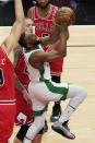 Boston Celtics guard Kemba Walker, right, drives to the basket past Chicago Bulls center Nikola Vucevic, front left, and center Daniel Theis, back left, during the first half of an NBA basketball game in Chicago, Friday, May 7, 2021. (AP Photo/Nam Y. Huh)