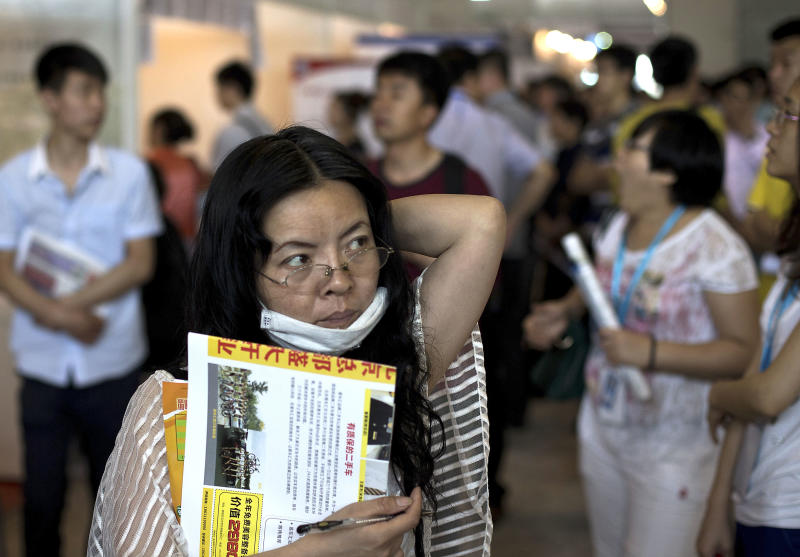 In this photo taken on May 25, 2013, a Chinese woman with her resume hunts for a job during a job fair held at the China International Exhibition Center in Beijing. While the job market in China is still much better than in many other parts of the world, 2013 is being billed locally as the worst for young graduates. A record number of them _ about 7 million _ are leaving universities and graduate schools to seek their first employment at a time when companies are hiring fewer people. Women appear to be faring worse than men. (AP Photo/Andy Wong)