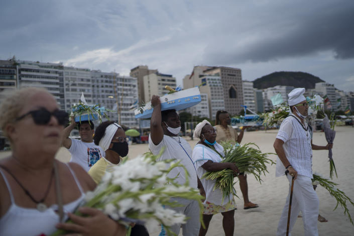Worshippers with offerings for Yemanja, goddess of the sea, walk on Copacabana beach during an an Afro-Brazilian ceremony that is part of traditional New Year's celebrations to plea for relief from the new coronavirus pandemic and asks for a better new year, in Rio de Janeiro, Brazil, Tuesday, Dec. 29, 2020. (AP Photo/Lucas Dumphreys)