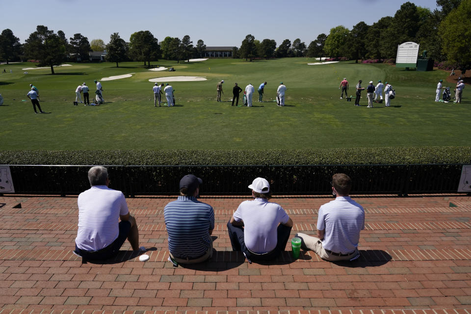 Patrons watch players warm up on the range before a practice round for the Masters golf tournament on Tuesday, April 6, 2021, in Augusta, Ga. (AP Photo/Charlie Riedel)