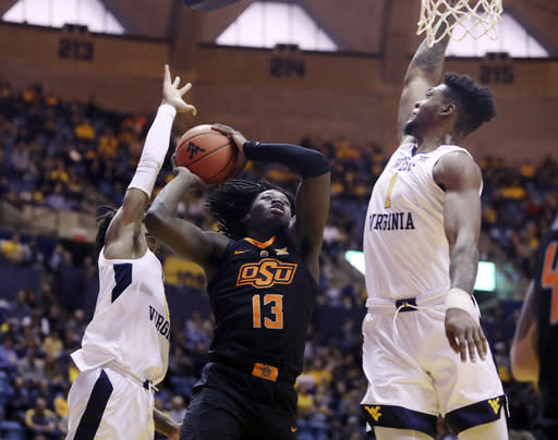 Oklahoma State guard Isaac Likekele (13) drives as West Virginia guard Trey Doomes (0) and forward Derek Culver (1) defend during the first half of an NCAA college basketball game Saturday, Jan. 12, 2019, in Morgantown, W.Va. (AP Photo/Raymond Thompson)
