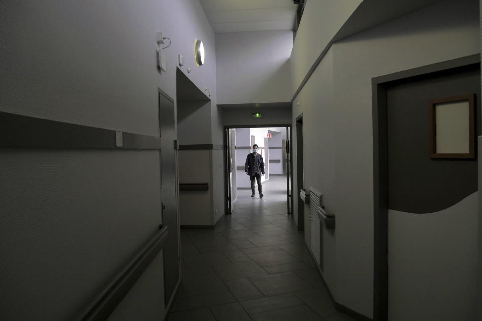 A patient walks on a corridor of the Rouvray psychiatric hospital, in Rouen, western France, Wednesday, Nov. 25, 2020. Lockdowns that France has used to fight the coronavirus have come at considerable cost to mental health. Surveying points to a surge of depression most acute among people without work, in financial hardship and young adults. (AP Photo/Thibault Camus)