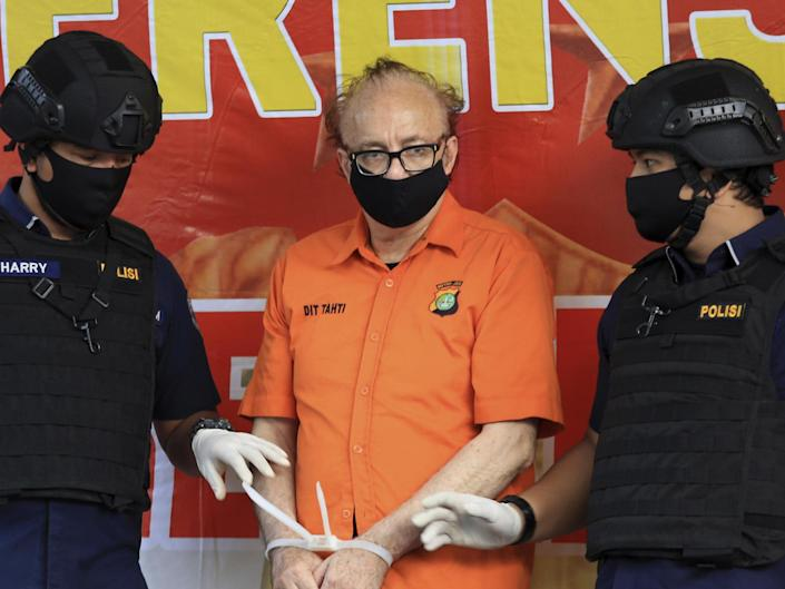 French national Francois Camille Abello flanked by police officers at a press conference in Jakarta, Indonesia, on 9 July, 2020: AP