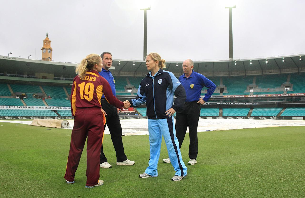 SYDNEY, AUSTRALIA - JANUARY 13: Captains Alex Blackwell of the Breakers and Jodie Fields of the Fire shake hands in the centre of the SCG after umpires called off play because of rain. NSW winning under the Duckworth- Lewis system. The WNCL Final match between the NSW Breakers and the Queensland Fire at the Sydney Cricket Ground on January 13, 2013 in Sydney, Australia.  (Photo by Craig Golding/Getty Images)