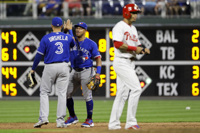 Toronto Blue Jays second baseman Yangervis Solarte, center, and shortstop Giovanny Urshela, left, celebrate past Philadelphia Phillies' Cesar Hernandez after a baseball game, Friday, May 25, 2018, in Philadelphia. (AP Photo/Matt Slocum)