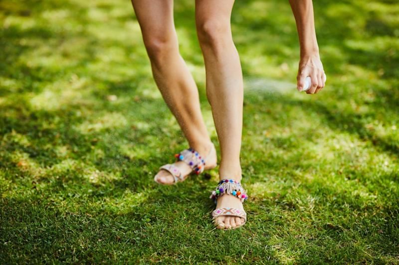woman's legs being sprayed with insect repellent outdoors