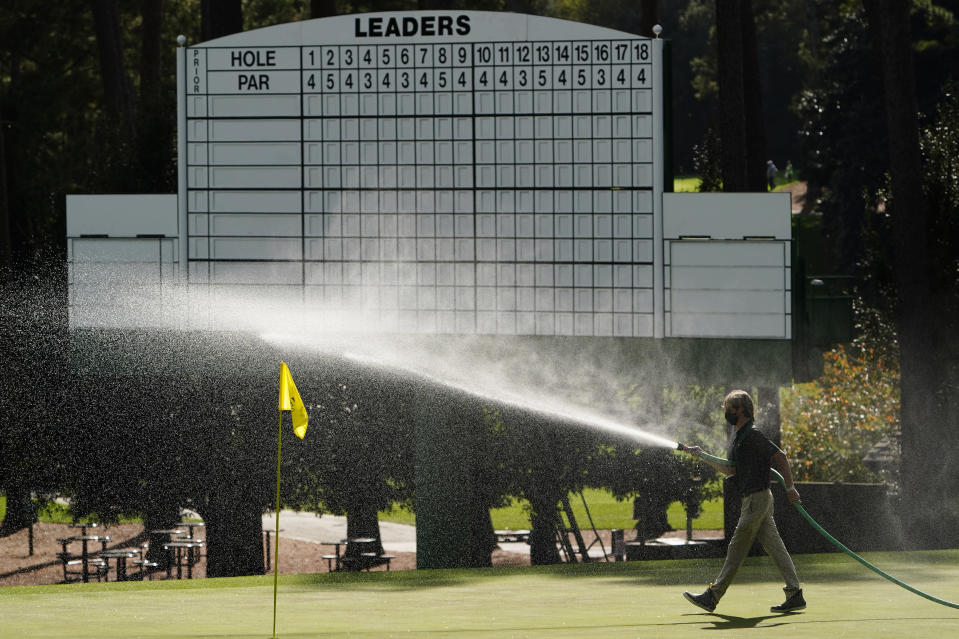 A course worker waters the third hole during a practice round for the Masters golf tournament Monday, Nov. 9, 2020, in Augusta, Ga. (AP Photo/Matt Slocum)