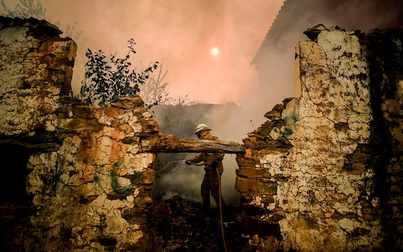 A National Guard Firefighter uses a hose during a wildfire on Roda village in Macao, central Portugal on July 21, 2019. | PATRICIA DE MELO MOREIRA/Getty Images
