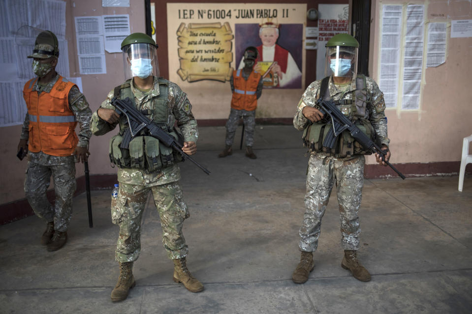 Soldiers stand guard outside a school during a COVID-19 vaccination campaign for the elderly in Iquitos, Peru, Thursday, March 18, 2021. (AP Photo/Rodrigo Abd)