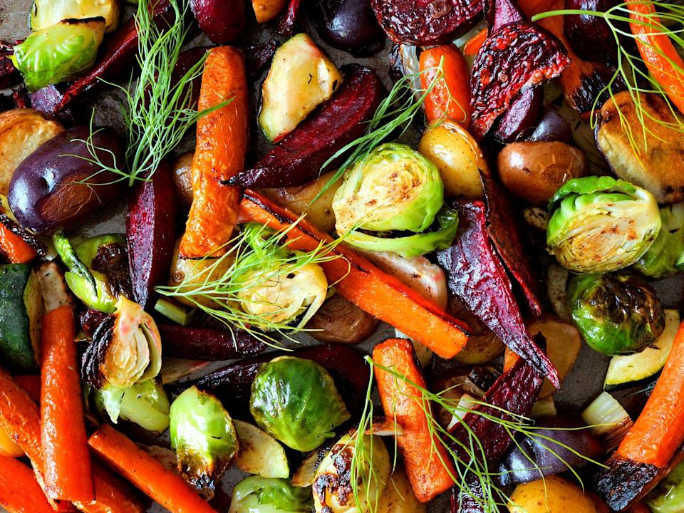 Roasted vegetables flay flat on a baking sheet.