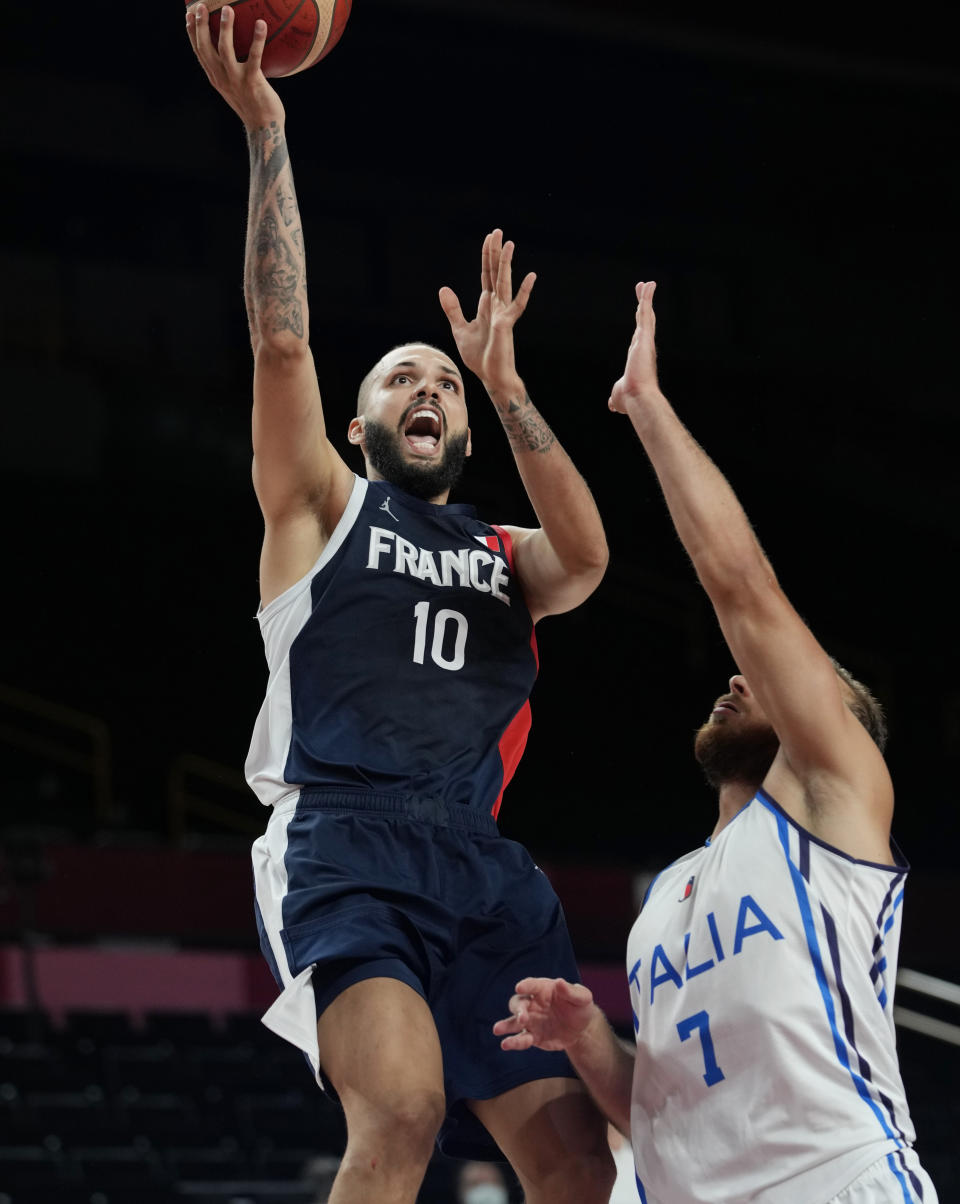 France's Evan Fournier (10) scores over Italy's Stefano Tonut (7) during a men's basketball quarterfinal round game at the 2020 Summer Olympics, Tuesday, Aug. 3, 2021, in Saitama, Japan. (AP Photo/Eric Gay)