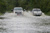 Pickup trucks pass each other on the flooded Cedar Lake Road in Biloxi, Miss., Saturday, June 19, 2021, as water from Tropical Storm Claudette begins to recede. Tropical Storm Claudette brought much evening and early morning rain and flooded various communities along the Mississippi Gulf Coast. (AP Photo/Rogelio V. Solis)