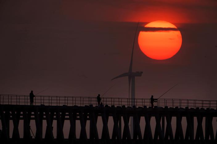 Fishermen on Blyth pier in Northumberland on Tuesday as thunderstorms - and hot weather - are set to continue. (PA)