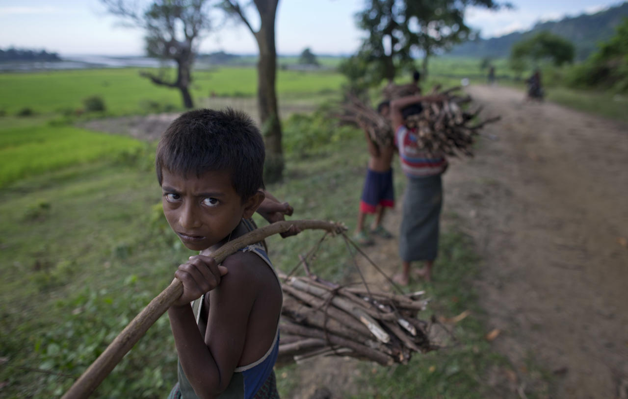 "In this Sept. 12, 2013 photo, Muslim children carry bundles of sticks collected from a near by forest to sell as firewood close to Zay Di village, Maungdaw, Rakhine state, Myanmar. In this corner of Myanmar tens of thousands of Rohingya children born out of wedlock are ""blacklisted"" and do not exist in the government's eyes. They cannot go to public schools or get treatment in the state-run hospital without paying exorbitant bribes. (AP Photo/Gemunu Amarasinghe)"