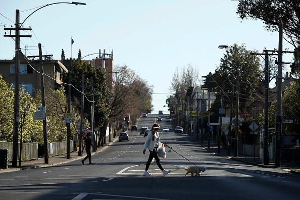 People exercise across a quiet Punt Road in Richmond in Melbourne, Australia.